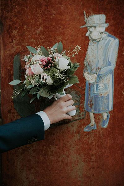 Brautstrauß in herbstlichen Farben wird vom Bräutigam ins Bild gehalten, man sieht nur seinen Arm